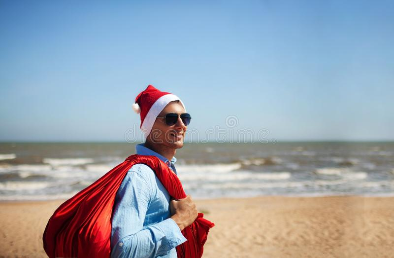 Christmas, holidays, travel and people concept - man in santa claus hat with gift box over tropical beach background. View from the back stock images