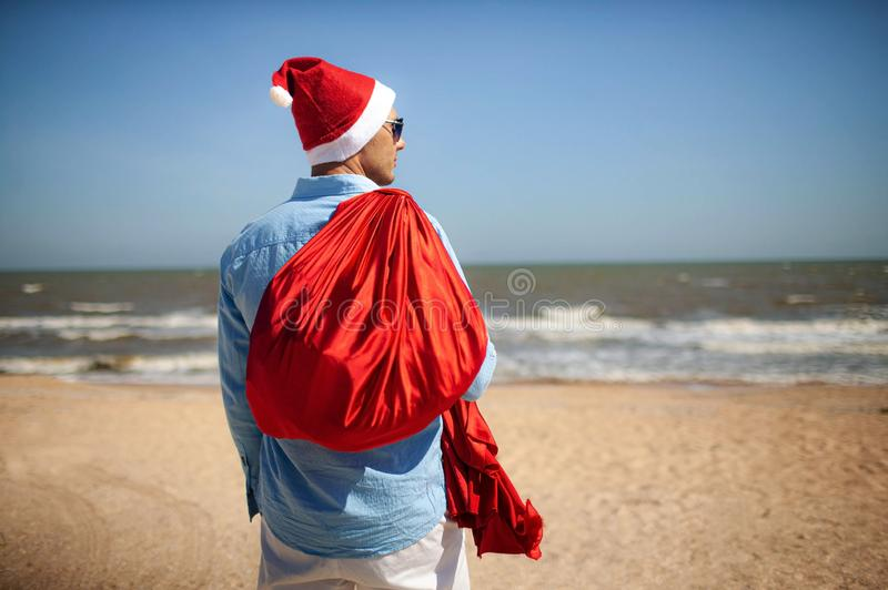 Christmas, holidays, travel and people concept - man in santa claus hat with gift box over tropical beach background. View from the back stock photo