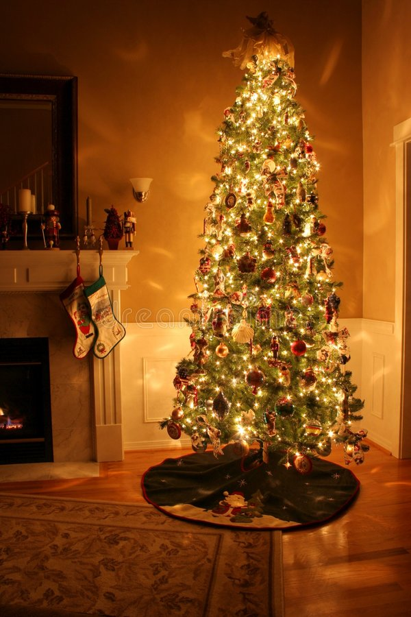 Christmas Home. A Chrismas tree by the fireplace lit up stock photos