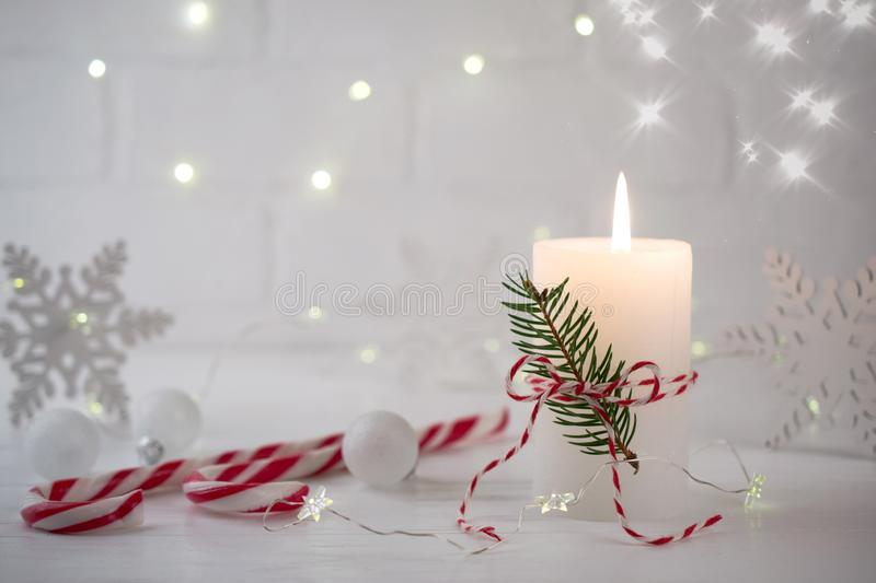 Christmas home decoration. Burning white candle and Christmas interior decorations on table royalty free stock photos