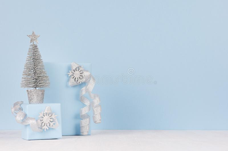 Christmas home decoration - silver fir with festive gift boxs with sparkles bows on white wood board and pastel blue wall. stock photo