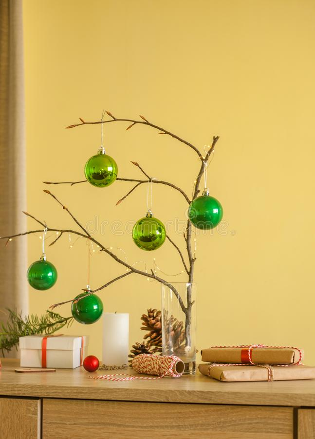 Christmas home decorations. Green balls, branch of tree, gift boxes, candle,pine cones, DIY idea for interior design. Christmas home decorations. Green balls stock photography