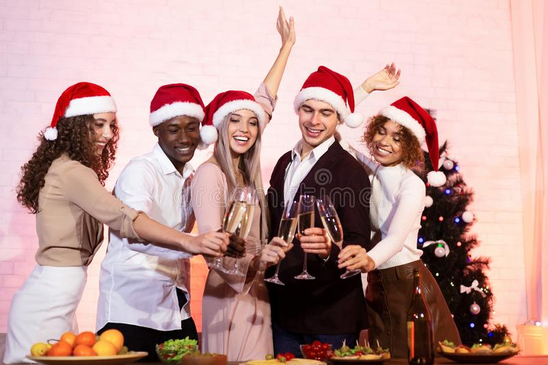 Happy Diverse Friends Celebrating Xmas Clinking Champagne Glasses Standing Indoor royalty free stock images