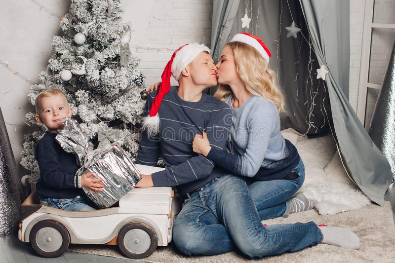 Christmas home portrait of a happy family. Boy holds a gift and sits on a typewriter. Mom and dad in Santa Claus hats kiss each other. Isolated against a stock images