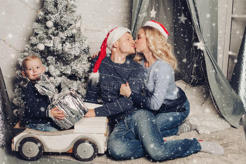 Christmas home portrait of a happy family. Boy holds a gift and sits on a typewriter. Mom and dad in Santa Claus hats kiss each other. Isolated against a royalty free stock photography