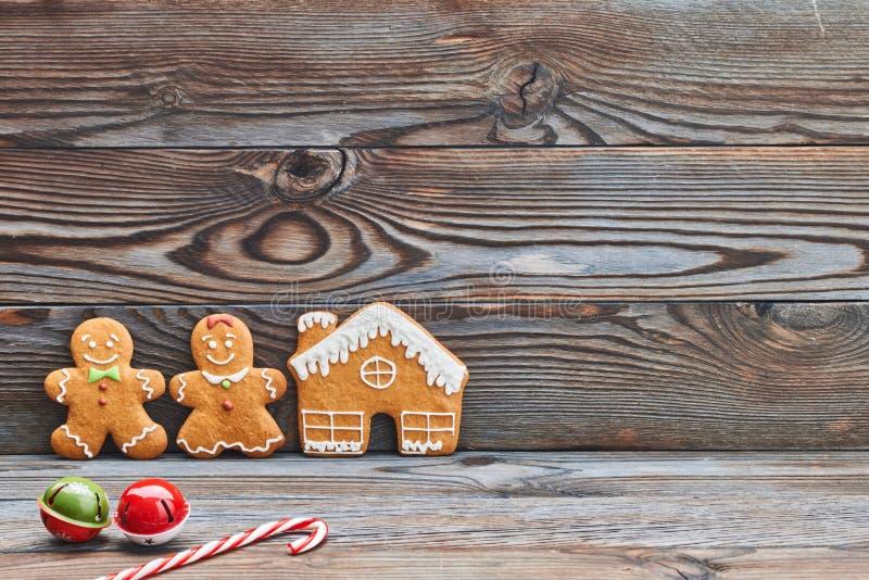 Christmas homemade decoration, gingerbread house and couple - man and woman. Christmas homemade gingerbread cookies and decoration on wooden background stock image