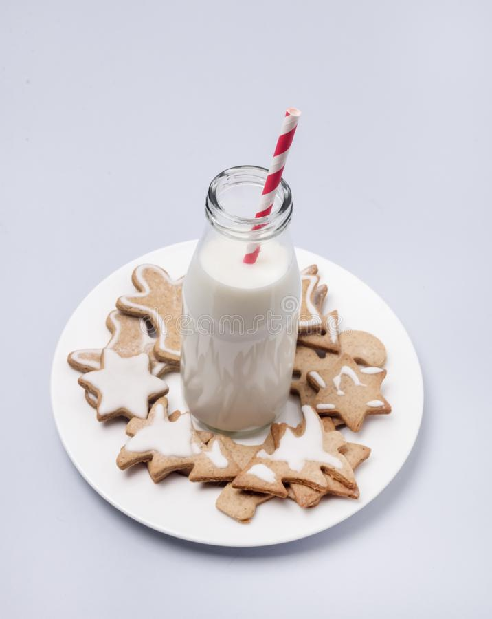 Christmas Homemade Gingerbread Cookies on Light Blue Background Holidays Concept Glass Bottle With Milk Red Straw Plate With Cooki stock image