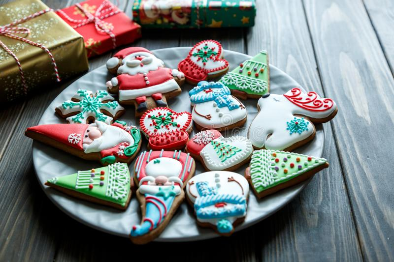 Christmas homemade gingerbread cookies, spices on the plate on dark wooden background among Christmas presents. Top view. holiday, celebration and cooking stock image
