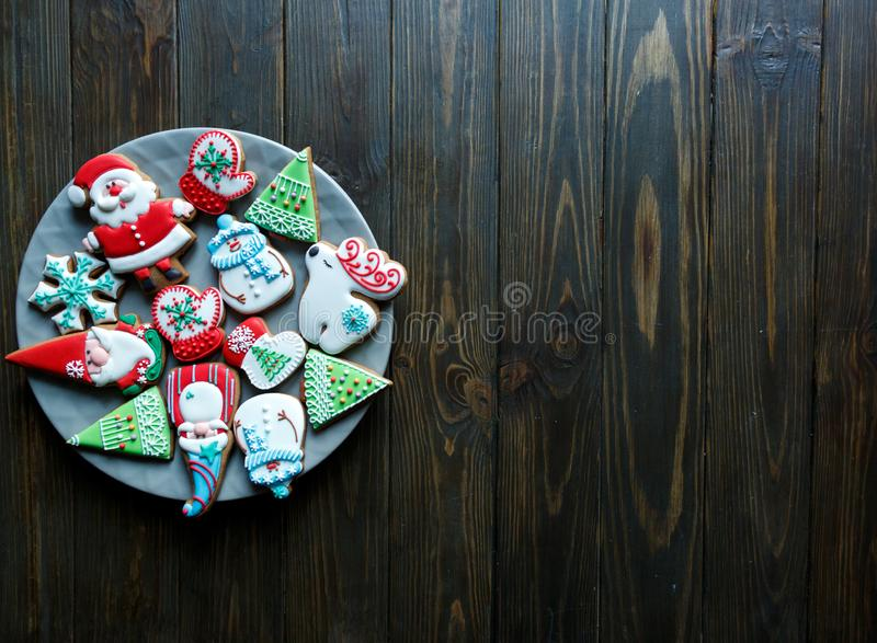 Christmas homemade gingerbread cookies, spices on the plate on dark wooden background among Christmas presents. Christmas homemade gingerbread cookies, on dark stock images