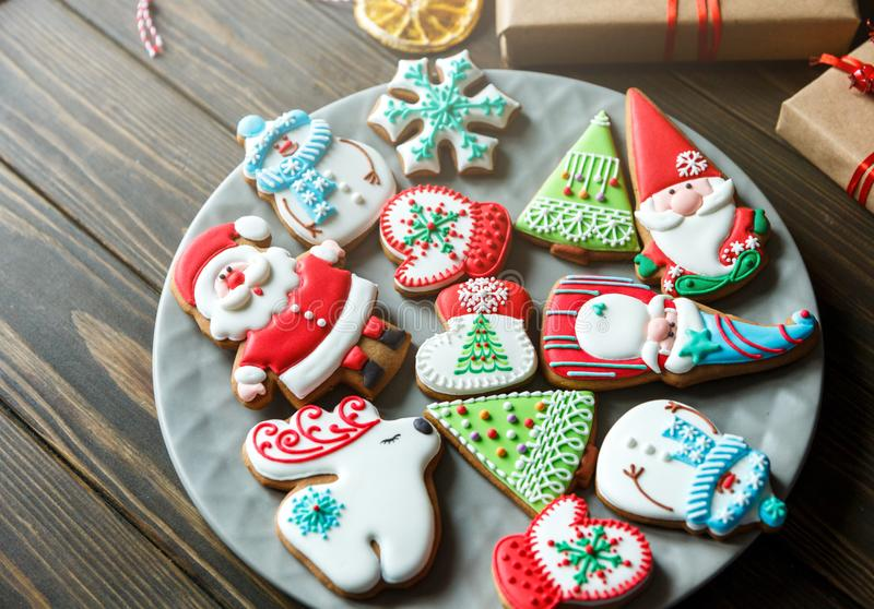 Christmas homemade gingerbread cookies, spices on the plate on dark wooden background among Christmas presents,. Top view. holiday, celebration and cooking stock photo