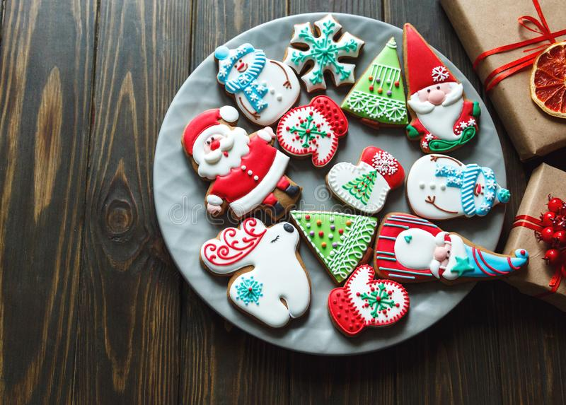 Christmas homemade gingerbread cookies, spices on the plate on dark wooden background among Christmas presents,. Top view. holiday, celebration and cooking stock image