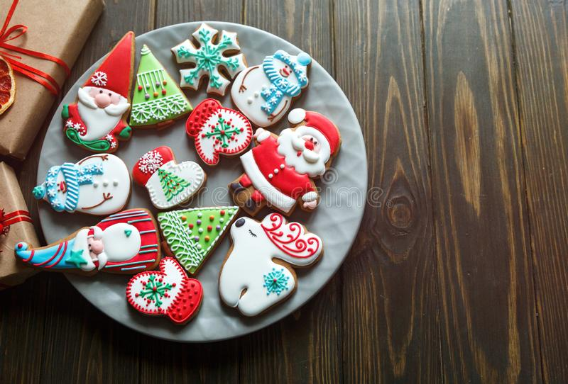 Christmas homemade gingerbread cookies, spices on the plate on dark wooden background among Christmas presents, top view. Holiday, celebration and cooking stock photo