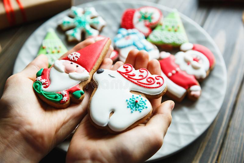 Christmas homemade gingerbread cookies, spices on the plate on dark wooden background among Christmas presents, top view. Holiday, celebration and cooking royalty free stock image