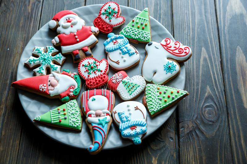 Christmas homemade gingerbread cookies, spices on the plate on dark wooden background among Christmas presents. Top view. holiday, celebration and cooking stock photo