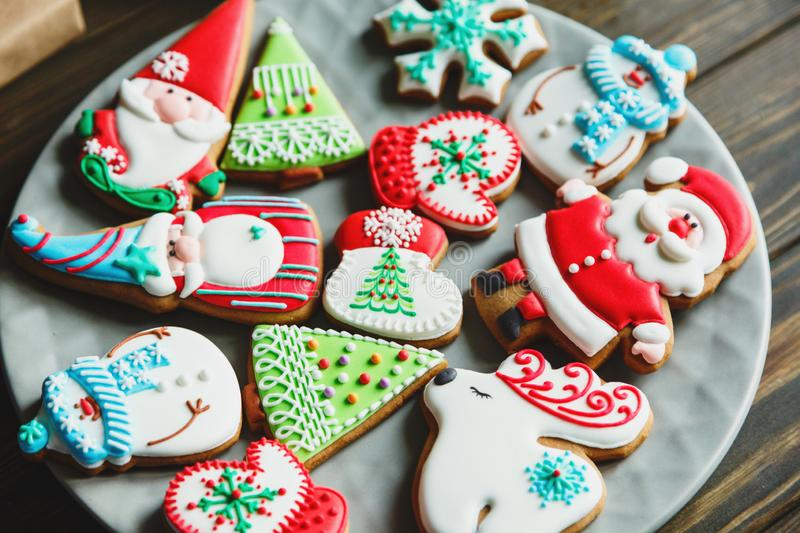 Christmas homemade gingerbread cookies, spices on the plate on dark wooden background among Christmas presents, top view. Holiday, celebration and cooking royalty free stock photography