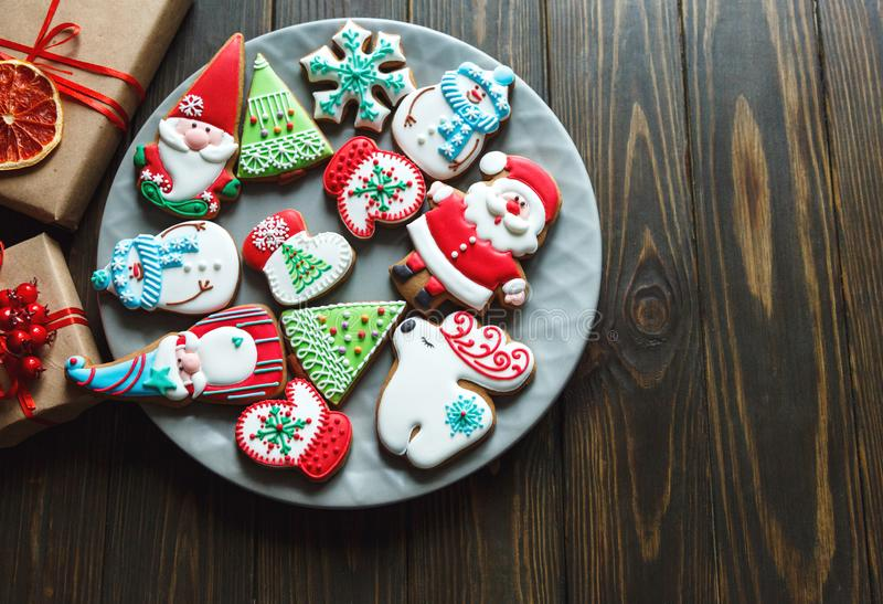 Christmas homemade gingerbread cookies, spices on the plate on dark wooden background among Christmas presents, top view. Holiday, celebration and cooking stock images