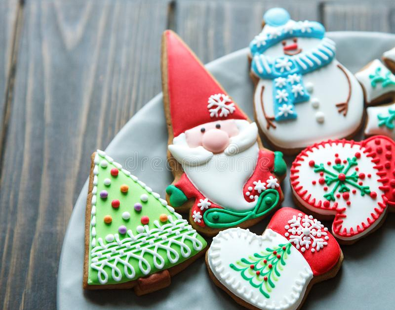 Christmas homemade gingerbread cookies, spices on the plate on dark wooden background among Christmas presents, top view. Holiday, celebration and cooking royalty free stock images