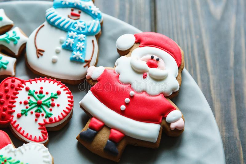 Christmas homemade gingerbread cookies, spices on the plate on dark wooden background among Christmas presents, top view. Holiday, celebration and cooking stock photography