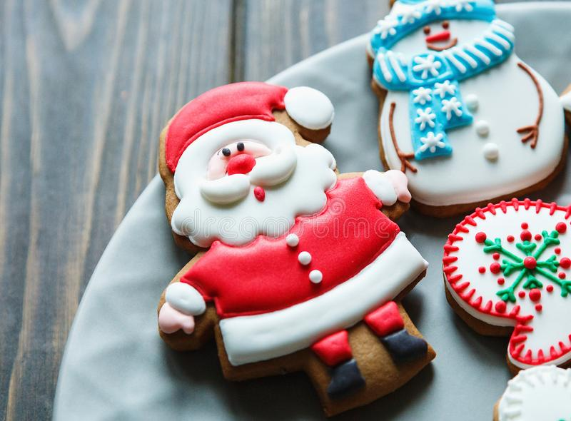 Christmas homemade gingerbread cookies, spices on the plate on dark wooden background among Christmas presents, top view. Holiday, celebration and cooking stock image