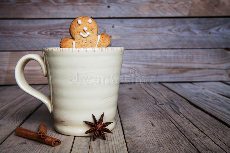 Christmas homemade gingerbread man on wooden background. Large cup of coffee. Cinnamon and star anise royalty free stock images