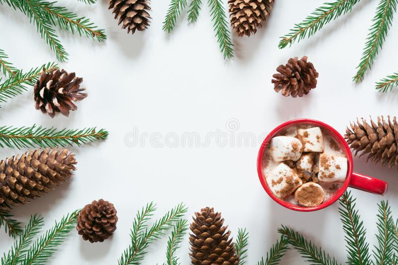 Christmas hot chocolate with marshmallows and christmas tree branches pine cone on the white. Top view with copy space. Christmas hot chocolate with royalty free stock images