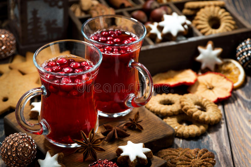 Christmas hot cranberry tea and cookies on dark table stock photo