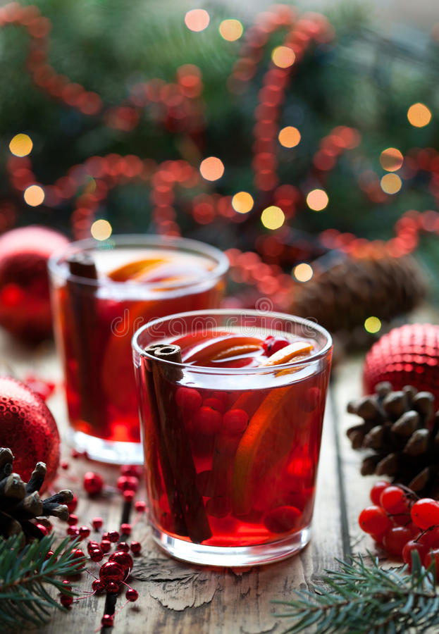 Christmas hot cranberry tea, orange pomegranate punch or mulled wine in a wooden table. Closeup. Winter tree decorations stock images