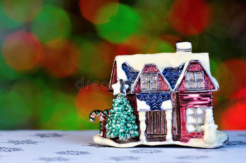 Christmas house background bright bokeh lights. White snow on the winter roof, a star on the Christmas tree, snowman winter royalty free stock photo