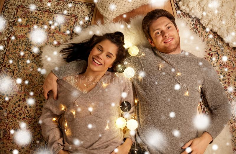 Happy couple with garland lying on floor at home royalty free stock images