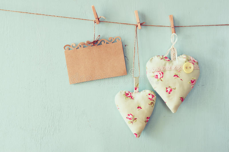 Christmas image of fabric hearts and empty card for adding text hanging on rope in front of blue wooden background. retro filtered stock image