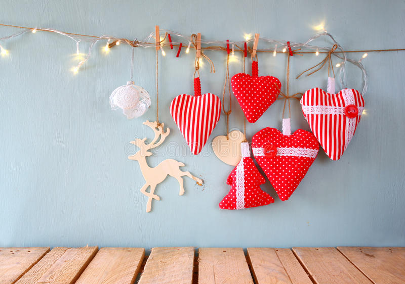 Christmas image of fabric red hearts and tree. wooden reindeer and garland lights, hanging on rope stock photo