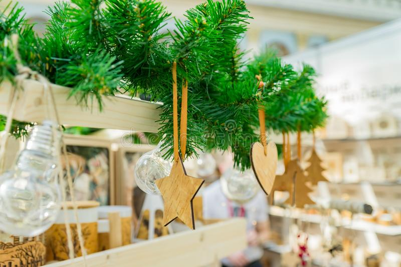 Christmas interior decoration. Wooden toys of different shapes star, heart, fur tree hanging on fur tree branch stock photos