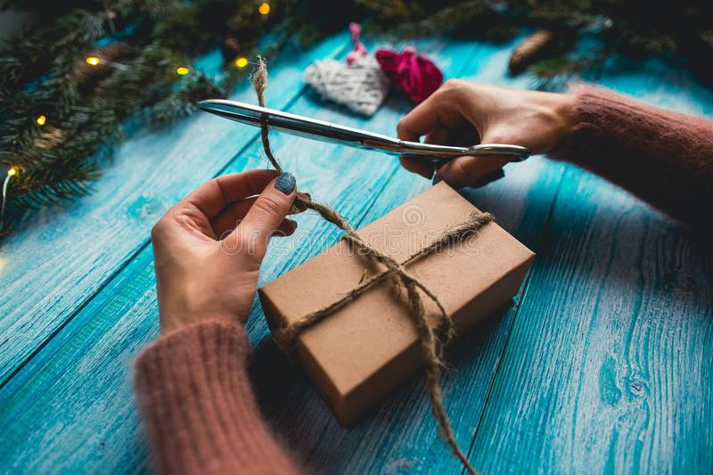 Christmas items on a blue wooden table. Woman`s hands wrapping Christmas gift. stock image