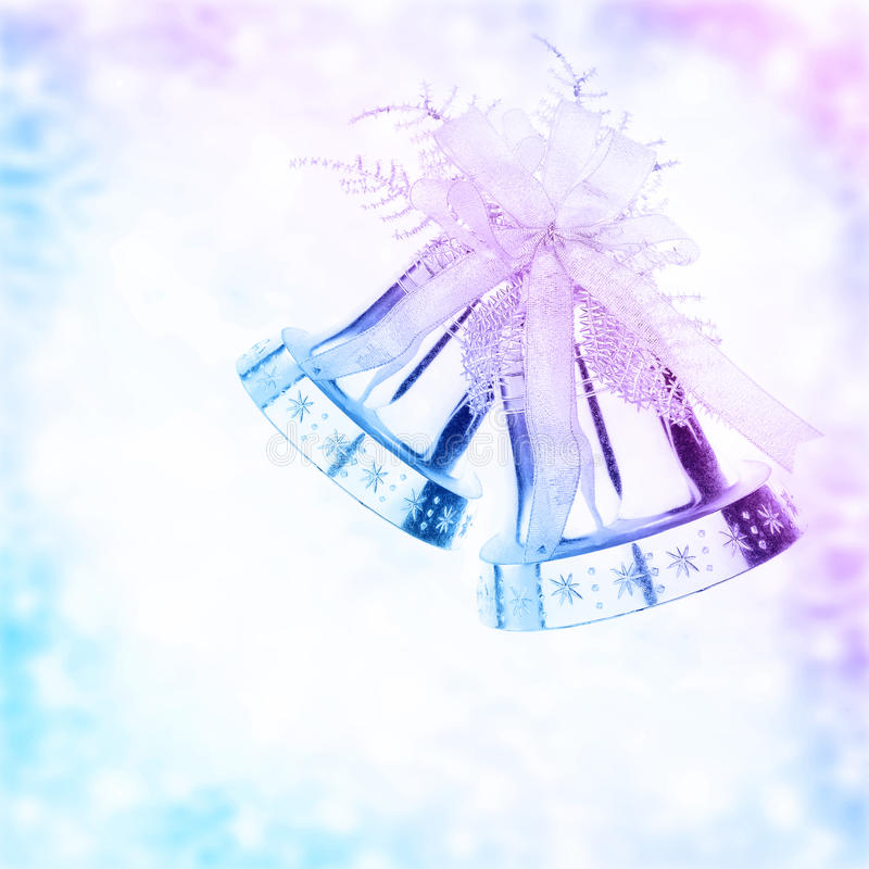 Christmas jingle bell border. Silver jingle bell border, Christmas tree ornament and holiday decoration isolated on blue and purple blurry background stock images