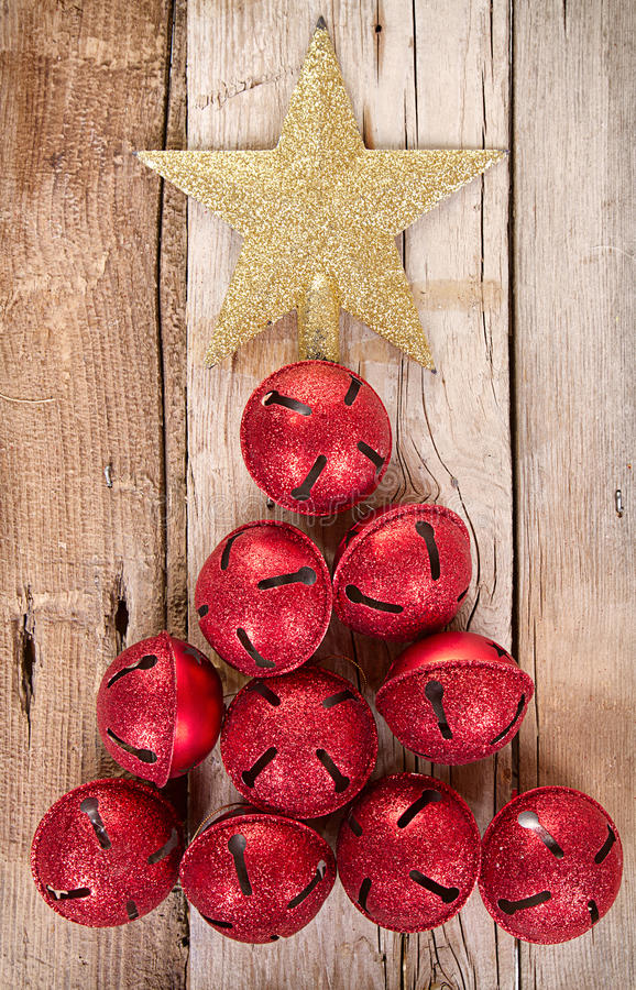 Christmas jingle bells and star shaped like a Christmas tree. On a rustic wooden background royalty free stock photo
