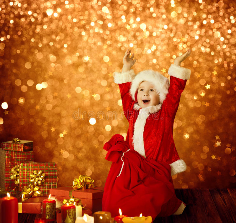 Christmas Kid, Happy Child Presents Gifts, Red Santa Bag, Boy Arms up. Christmas Kid, Happy Child Presents Gifts and Red Santa Bag, Boy Arms up, Golden Xmas stock photos