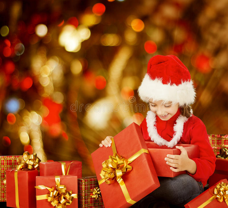 Christmas Kid Opening Present Gift Box, Happy Child in Santa Hat royalty free stock images
