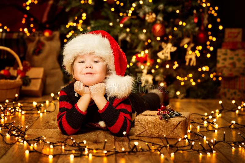 Christmas Kid in Red Hat, Happy Child Portrait in Decorated Lighting Room, Baby Boy Xmas present gift. Christmas Kid in Red Hat, Happy Child Portrait in royalty free stock images