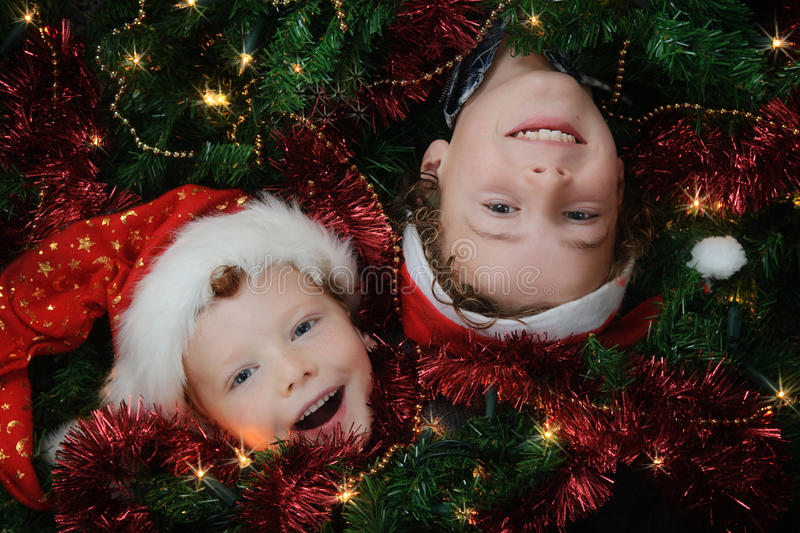 Christmas Kids. Two happy boys lying between christmas decoration and lights, wearing Christmas hats royalty free stock image