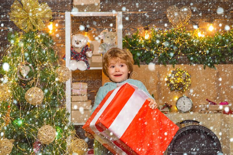 Christmas kids - happiness concept. Little Santa Claus gifting gift. Home Christmas atmosphere. Cheerful cute child royalty free stock photos