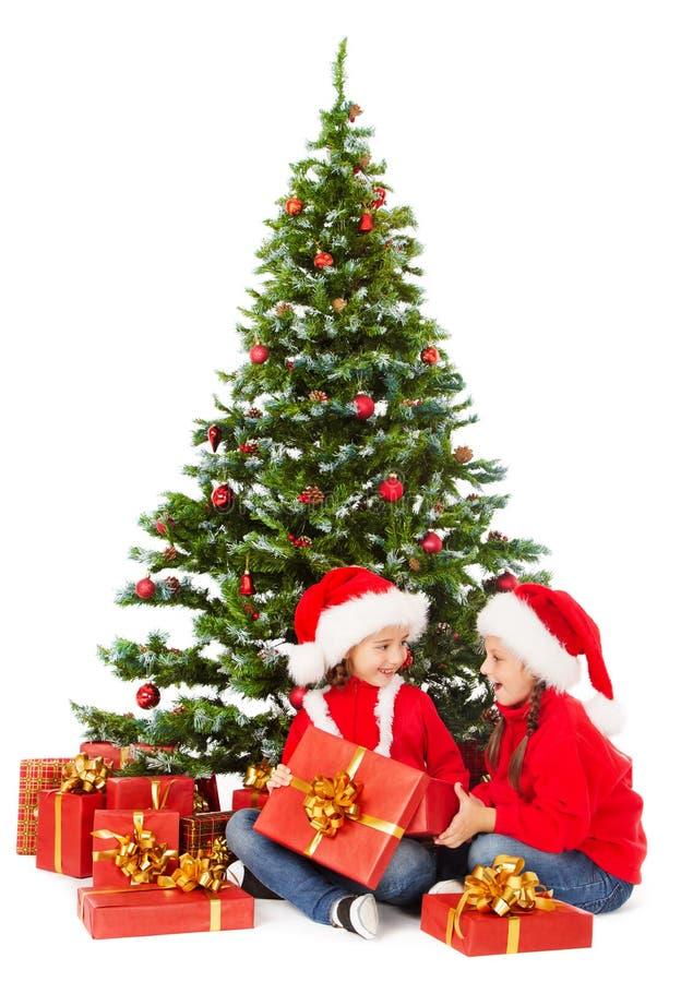 Christmas kids in Santa hat under xmas tree, open present gift box. Christmas kids in Santa hat sitting under xmas fir tree, open present gift box royalty free stock image