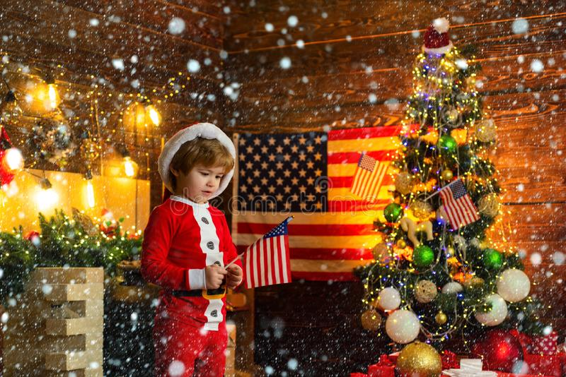 Christmas kids story in America. Happy cute boy waving American flag, wearing red costume. US Christmas. Independence in. A new home on New Year stock photo
