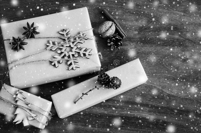 Christmas Kraft Boxes with Gifts Decorated in Rustic Style on Wooden Background. Vintage Image with Drawn Snowfall. stock image