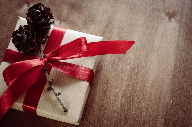 Christmas Kraft boxes with gifts, tied with red ribbons and pine cones in rustic style. royalty free stock photography