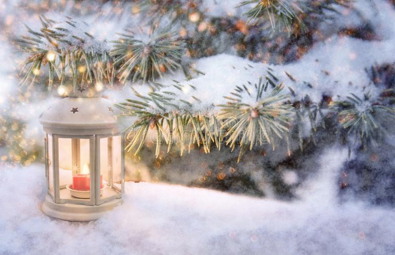 Christmas lantern with burning candle shines on snow and spruce branches, snowfall winter scene with light and bokeh. Close up stock photo