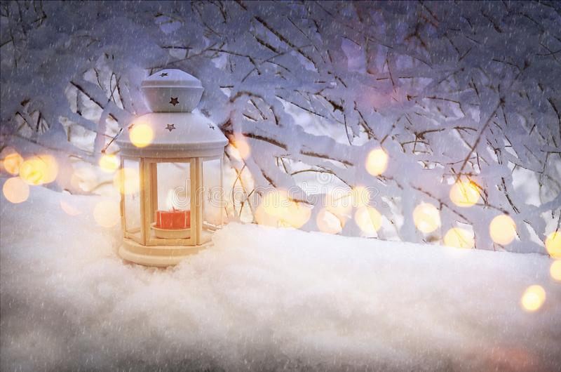 Christmas lantern with burning candle shines on snow and tree branches with yellow bokeh. Winter season and snowfall. Christmas lantern with burning candle royalty free stock photo