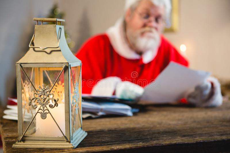 Christmas lantern and Santa Claus in background. At home stock images