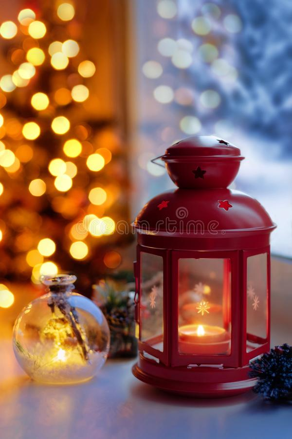 Christmas lantern by the window. Candle lantern on the windowsill. Evening lights under the tree. royalty free stock images