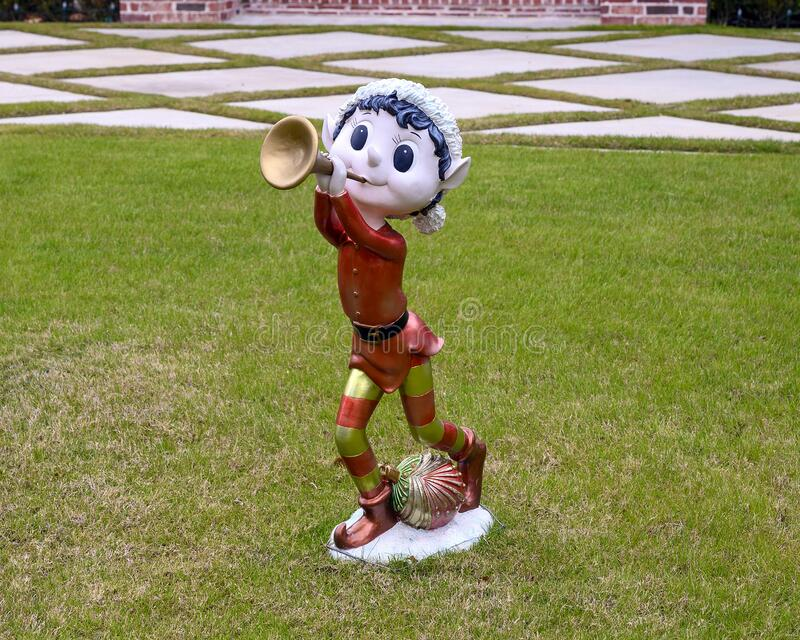Christmas lawn decoration with elf playing a trombone with an ornament between his feet in Dallas, Texas royalty free stock photo