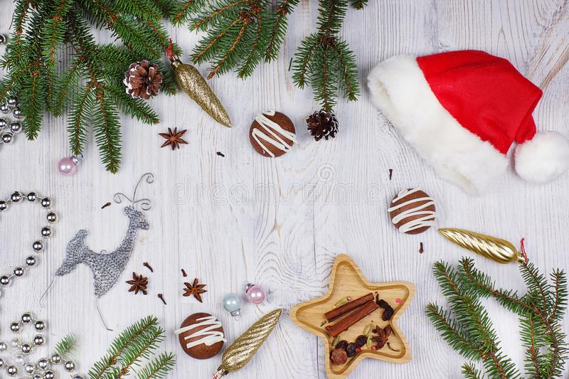 Christmas layout with copy space for text, Santa hat, decorations and Christmas tree branches and a deer on a light wooden backgro royalty free stock photo